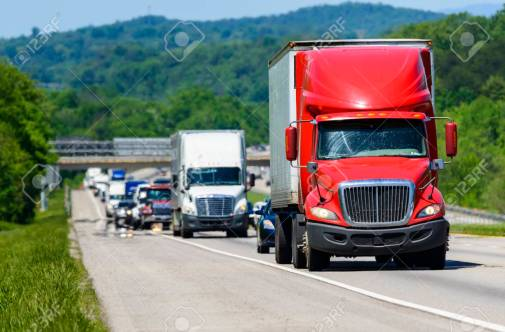 Red Semi Leads Traffic Down An Interstate Highway